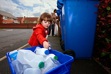 Young girl and mother recycling plastic and cardboard in street, Derbyshire, UK, April, Model released  -  Chris O'Reilly/ npl