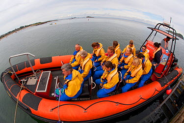 Group of tourists wearing waterproof clothing and life jackets in zodiac boat for seabird safari tour around Bass Rock, North Berwick, Firth of Forth, Lothian, Scotland, UK, August 2011  -  Peter Cairns/ 2020V/ npl