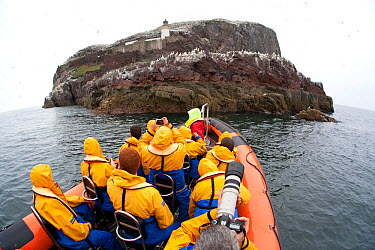 Group of tourists wearing waterproof clothing and life jackets photograph Gannet colony from zodiac boat on tour around Bass Rock, North Berwick, Firth of Forth, Lothian, Scotland, UK, August 2011  -  Peter Cairns/ 2020V/ npl