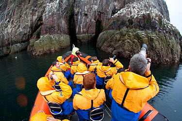 Group of tourists wearing waterproof clothing and life jackets photograph seabirds from zodiac boat on tour around Bass Rock, North Berwick, Firth of Forth, Lothian, Scotland, UK, August 2011  -  Peter Cairns/ 2020V/ npl