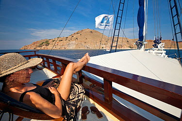 Woman relaxing on the sun deck of a yacht, Indonesia, August 2009 Model released No property release  -  Michele Westmorland/ npl