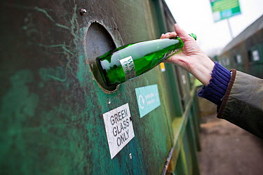 Person putting a glass bottle into a recycling bank at a recycling centre, Stroud, Gloucestershire, UK, February 2008  -  Nick Turner/ npl
