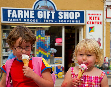 Children enjoying ice-creams with tourist souvenir shop in background, Seahouses, Northumberland  -  Uncatalogued/ npl