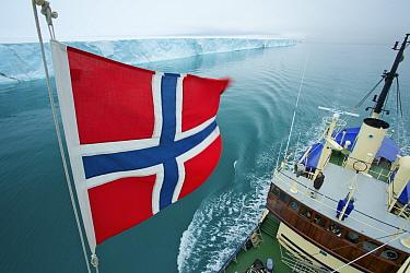 Norwegian flag set on M, S Stockholm and ice front of Brasvellbreen seen from crow's nest, Austfonna, Nordaustlandet, Svalbard, Norway, July 2012  -  Florian Mollers/ npl