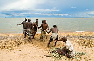 Young men and boys hauling in fishing boat half a kilometre out at Lake Malawi, Chipoka, Malawi February 2008  -  Will Watson/ npl