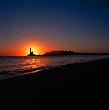 Sunrise and lighthouse at the entrance to Olbia harbour, Sardina Mediterranean  -  Michael Pitts/ npl