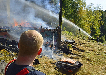 Firemen extinguishing controlled fire in abandoned house during training exercise whilst another rests and cooks sausages on a barbeque, Akerhus, Norway, September 2013  -  Pal Hermansen/ npl