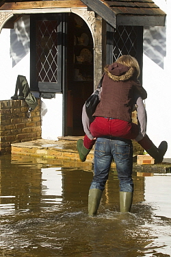 Resident giving a piggy back ride outside flooded home during February 2014 flood Surrey, England, UK, 16th February 2014  -  David Woodfall/ npl