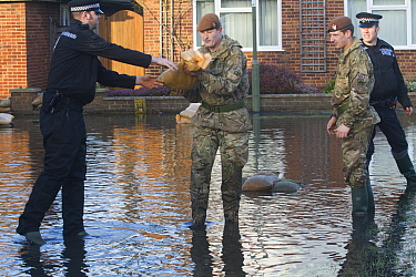 Army and police in flooded street after February 2014 flooding, helping to provide support for the residents and supplying sand bags, Chertsey, Surrey, England, UK, 16th February 2014  -  David Woodfall/ npl