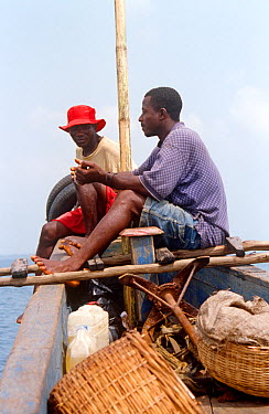Man with shell to blow to announce departure and arrival on boat journey to Bunce island Sierra Leone, 2004-2005  -  Steve O. Taylor/ npl