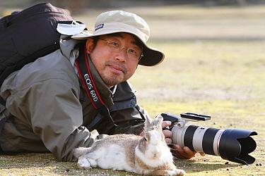 Photographer Yukihiro Fukuda, lying on the ground with a rabbit, Okunoshima Rabbit Island, Takehara, Hiroshima, Japan  -  Yukihiro Fukuda/ npl