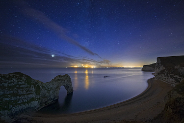 Stars and Milky Way over Durdle Door and the Jurassic Coast, with the lights of Weymouth and Portland beyond, Dorset, England, UK, December 2013  -  David Noton/ npl