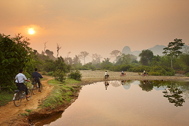 Children riding bikes along riverside path at dawn, near Vang Vieng, Laos, March 2009  -  David Noton/ npl