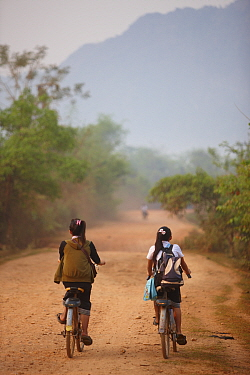 Children cycling to school, near Vang Vieng, Laos, March 2009  -  David Noton/ npl