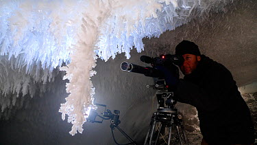 Cameraman Gavin Thurston filming ice crystals under volcanic ice cave, Mount Erebus, Antarctica Taken on location for BBC Frozen Planet series, 2009  -  Chadden Hunter/ npl