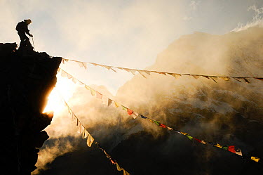 Climber on Kala Pattar peak (5545m) with Buddhist prayer flags at sunset Sagarmatha National Park UNESCO World Heritage Site, Khumbu, Everest Region, Nepal, Himalaya October 2011 Winner of Mountain Ac...  -  Enrique Lopez Tapia/ npl