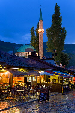 Restaurants lining 'Pigeon Square' in front of Bascarsija Mosque, illuminated at dusk, Old Town, Bascarsija district, Sarajevo, Bosnia and Herzegovina, Balkans 2007  -  Gavin Hellier/ npl