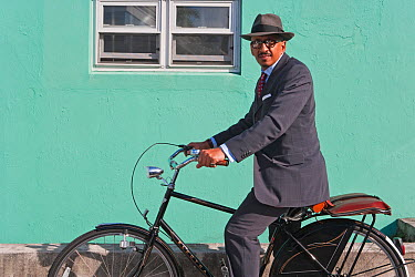 Businessman riding his bicycle in front of a colourfully painted wall, Hamilton, Bermuda, 2007 model released  -  Gavin Hellier/ npl