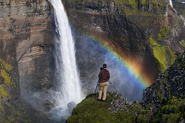 Photographer by the Haifoss waterfall with a rainbow in the spray, Iceland, August 2010