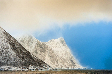 Snow squall falling on coastal mountains. Tortenberget across Ballesvika, Senja, Norway, February 2012.