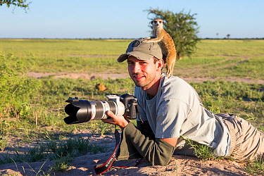 Meerkat (Suricata suricatta) using photographer Will Burrard-Lucas as a lookout post, Makgadikgadi Pans, Botswana. Model released.