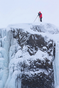 Photographer with tripod on edge of Godafoss warterfall, frozen in winter, Iceland, February 2014.