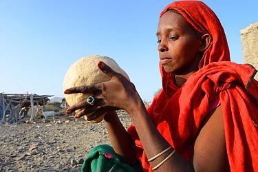 Afar tribe woman kneading a bread loaf before baking it, Malab-Dei village, Danakil depression, Afar region, Ethiopia, March 2015.