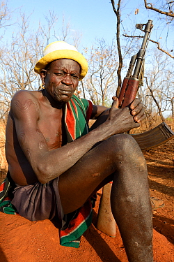 Older man from the Bodi tribe displaying elaborate skin scarifications, and holding Kalashnikov gun. The ones on his shoulder are for enemies he killed, the circles on the arm are for big game he hunt...