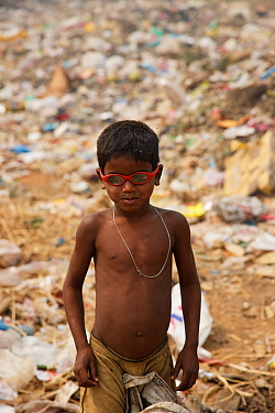 Young rag-picker boy with sunglasses at landfill site,  Guwahti, Assam, India, March.