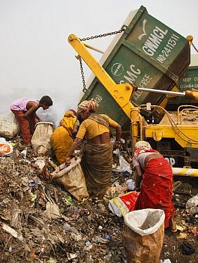 Rag-picker women sorting through rubbish at landfill site, Guwahti, Assam, India, March 2009.