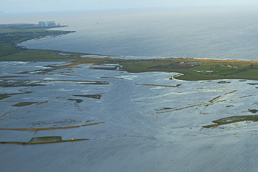 Aerial view of Steart Marshes Wildfowl and Wetland Trust Nature Reserve with Hinkley Point nuclear power station in background, Somerset, UK, February 2015. This area has been allowed to flood by the...
