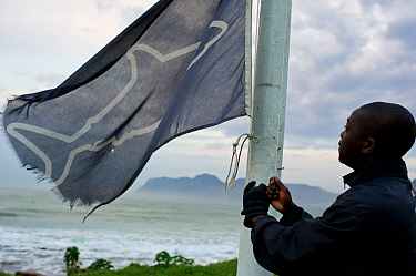 Dennis Chikodze hoists the black flag at the Kalk Bay post. It provides a warning to ocean goers that visibility is bad and the shark spotters may not see a white shark if it does enter the bay.  West...