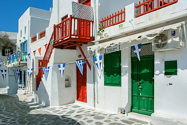 Picturesque alley in Mykonos Town with white houses, green doors and red balconies decorated with the Greek flag bunting, Mykonos Island, Cyclades, Aegean Sea, Mediterranean, Greece, August 2007.