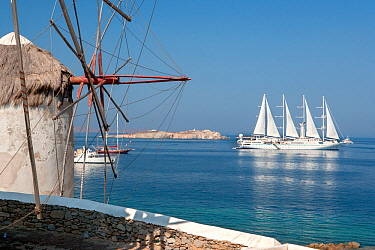 Traditional windmill, and luxury ship Wind Star, which is a sleek, 4-masted sailing yacht. Mykonos Island, Cyclades, Aegean Sea, Mediterranean, Greece, August 2007