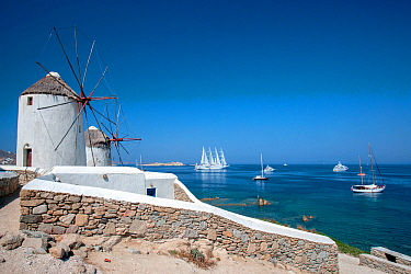 Traditional windmills, and luxury yachts, including the luxury ship Wind Star, which is a sleek, 4-masted sailing yacht. Mykonos Island, Cyclades, Aegean Sea, Mediterranean, Greece, August 2007