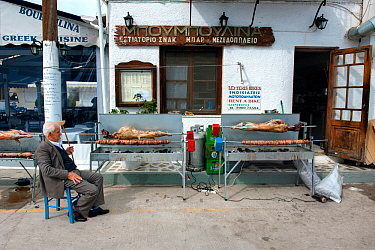 Man sitting outside a taverna, watching  whole lamb and Kokoretsi (offal sausage) cooking on a spit, in preparation for Easter Sunday meal. Spetses Island, Aegean Sea, Greece, Mediterranean, April 200...