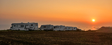 Motorhomes parked along the Normandy coast at sunset with view over the sea, France, September 2014.