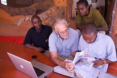 Iain Douglas-Hamilton and Save the Elephants team looking at Save the Elephants database and files, Kenya. Model released