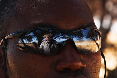 Ole Jorgen Liodden, reflected in man's sunglasses on safari, Botswana, November 2010.