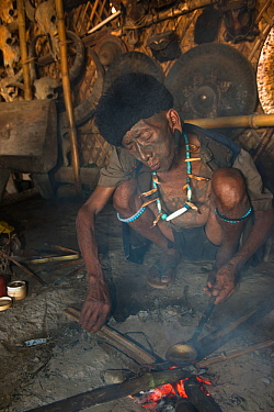 Konyak Naga man preparing opium to smoke. Mon district. Nagaland,  North East India, October 2014.
