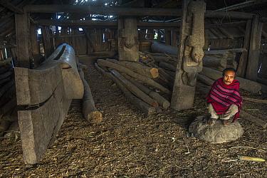 Konyak Naga man crouching by Hongphoi Village Log drum. Mon district. Nagaland,  North East India, October 2014.