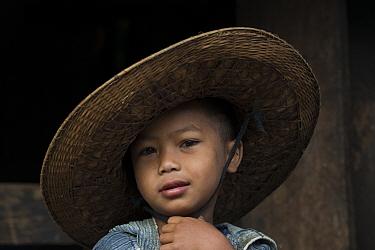 Khasi boy wearing straw hat, Nongriat, Khasi Hills. Meghalaya, North East India, October 2014.