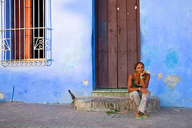 Local woman sitting in front of her house,  Camaguey, Cuba, Caribbean Sea, Atlantic Ocean. November 2007.