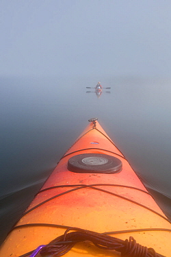 View from kayak to woman in another kayak ahead, Shoshone Lake, Yellowstone National Park, Wyoming, USA, August 2014. Model released.