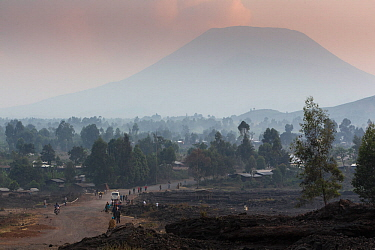 Road built along the path of the latest lava flow, leading towards Nyiragongo volcano silhouetted in the background, Virunga National Park, Democratic Republic of the Congo, August 2010.