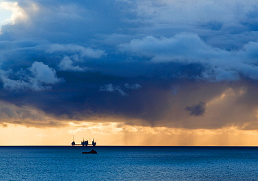Dark clouds at sunset over he silhouetted Oseberg oil rig, North Sea, Norway, September 2014.
