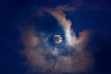 Full moon behind clouds, seen from Norfolk, England, UK, January 2010.