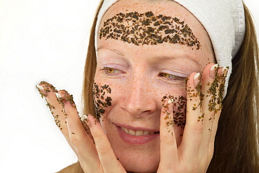 Woman applying Kelp (Laminaria  sp) to her face as part of beauty treatment. Kelp is used by comestic company Oceanwell to create various skin care products. July 2015. Model released