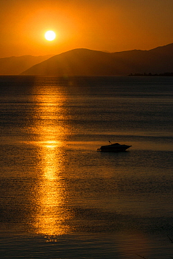 Sunset reflected on the surface of the Aegean Sea on a calm day with a speedboat, Evia Island, Greece. July 2014.