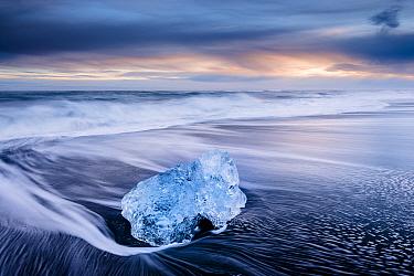 Ice on black volcanic sand beach with waves, Jokulsarlon, Southeast Iceland, February.
